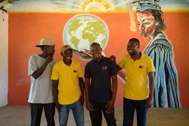 Bakari in the library classroom, with Mr. Mlonda, Mr. Dzengo and Sudi, who painted the mural.